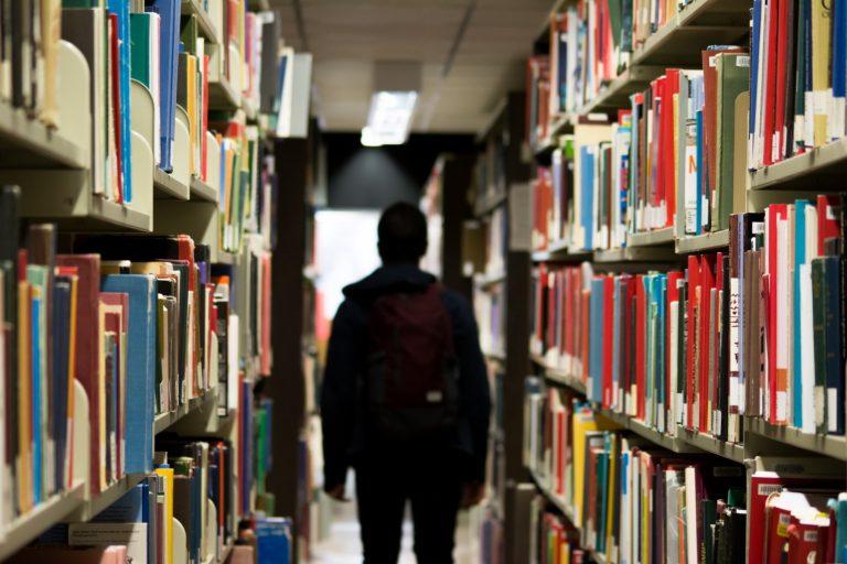 Silhouette d'ado de dos au milieu d'un couloir de bibliothèque