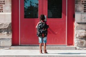 Petit garçon attend devant la porte de l'école