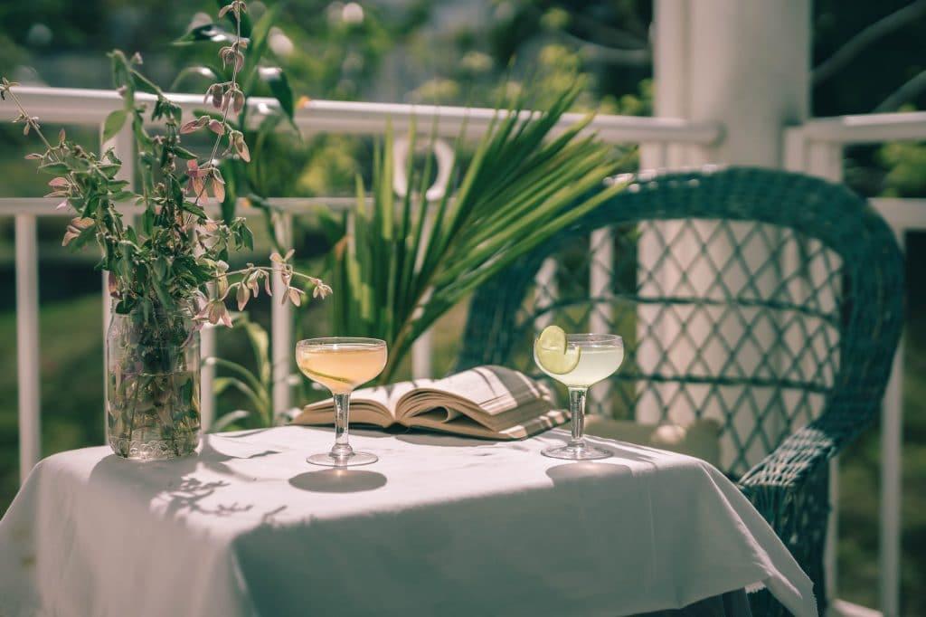 2 daiquiris avec un livre ouvert sur une table blanche ensoleillée