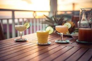 3 cocktails daiquiri sur une table au soleil couchant