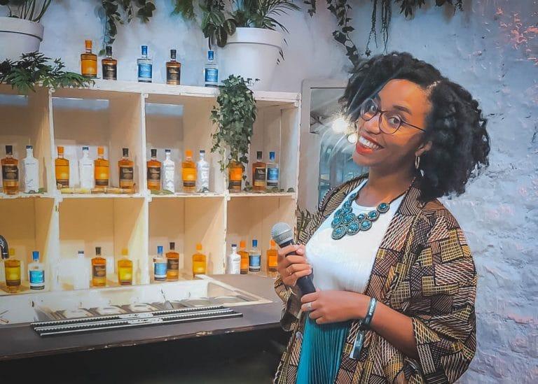 Audrey Bruisson facing shelvings of rum bottles