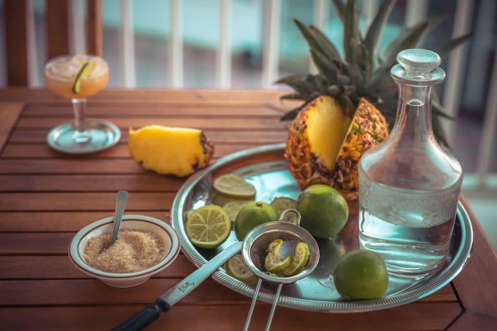 ingredients for a cocktail preparation with rum, lime, sugarcane and pineapple