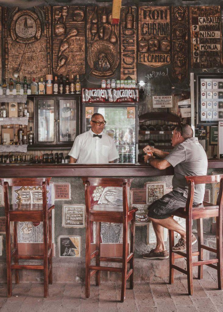 A Cuba, un barman et son client assis au comptoir